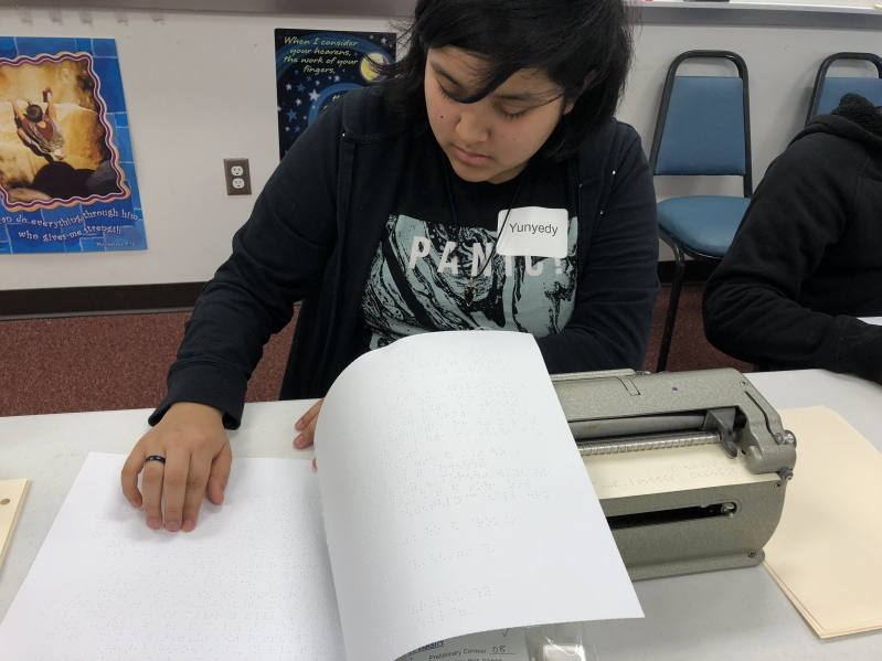 A female student in a navy hoodie reading braille text during a Braille Challenge activity with a Perkins braille writer in front of her.