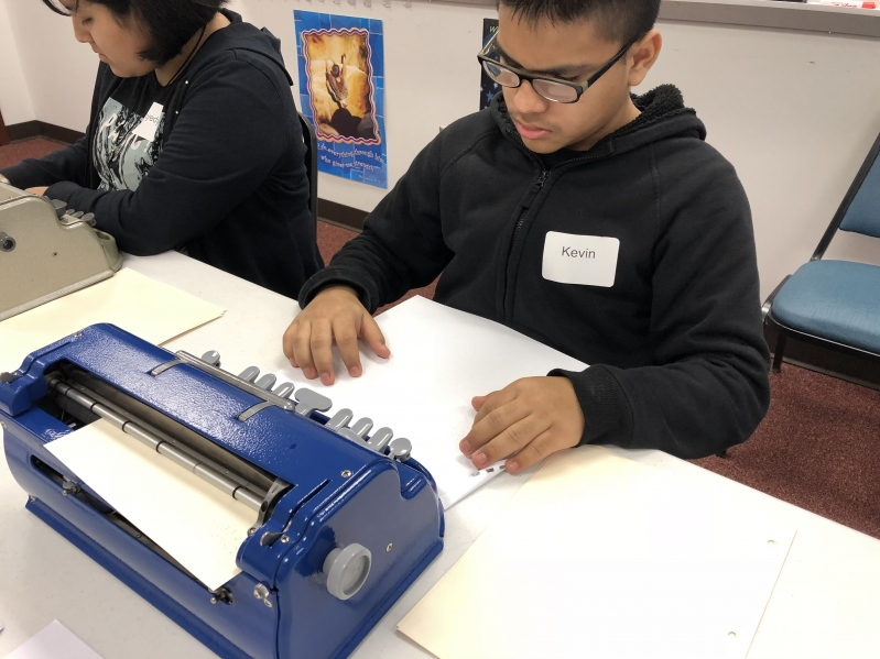A male student in a navy hoodie reading braille text during a Braille Challenge activity with a Perkins braille writer in front of him.