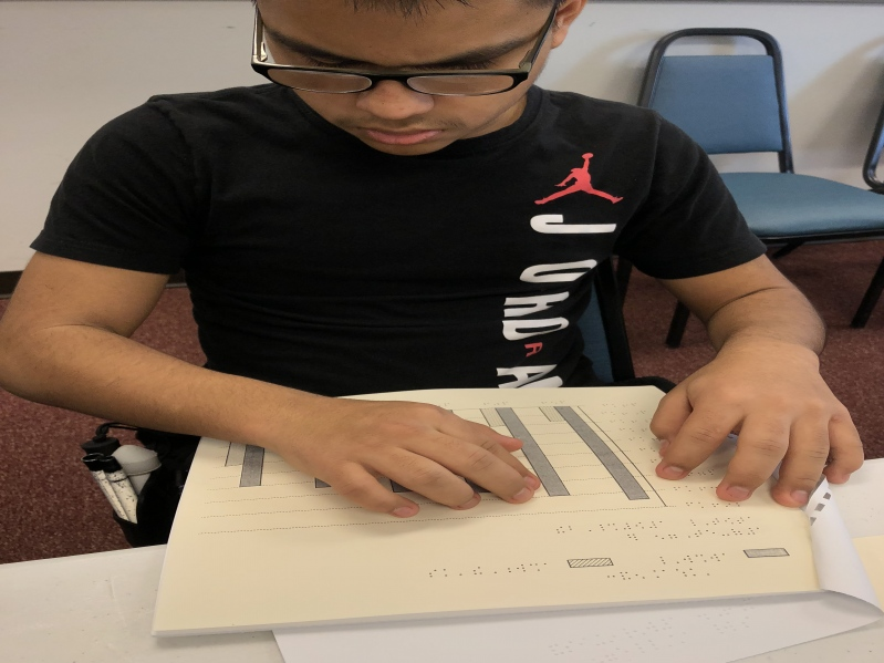 A male using two hands to scan and read a tactile graphic representation of a data column chart.