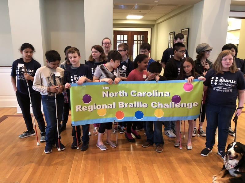 All Braille Challenge student participants gathered behind a banner with the text: North Carolina Regional Braille Challenge posing for a group picture.