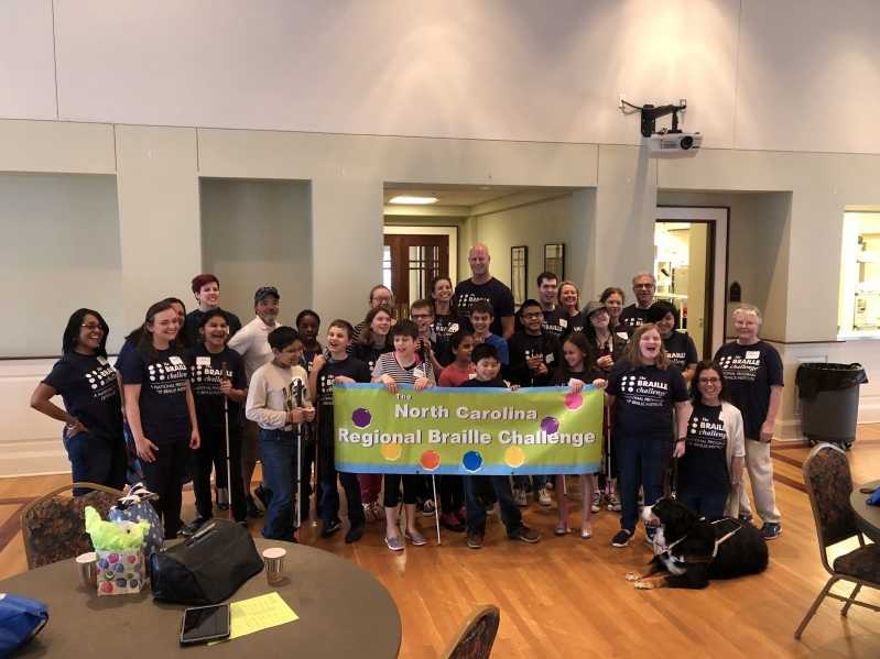 Student participants and volunteers gathered behind a banner with the text: North Carolina Regional Braille Challenge posing for a group picture.